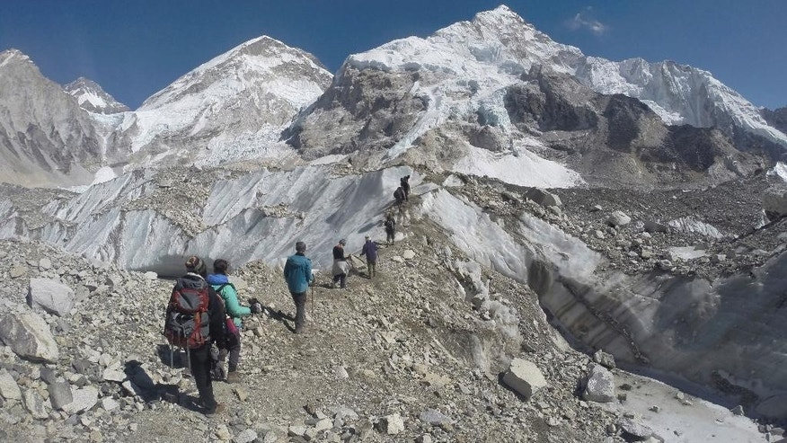 FILE - In this Monday, Feb. 22, 2016 file photo, international trekkers pass through a glacier at the Mount Everest base camp, Nepal. A Nepal official says some 30 climbers have gotten frostbite or become sick on Mount Everest, in addition to two who died in recent days on the world's highest mountain. (AP Photo/Tashi Sherpa, file)