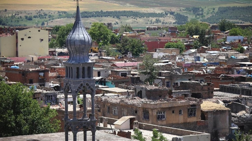 Many of the buildings and roof-tops show recent damage from recent military clashes in parts of the historic district of the mainly Kurdish city of Diyarbakir, southeastern Turkey, Sunday, May 22, 2016.  Turkish authorities have lifted a long-standing curfew from parts of the historic district famed for its ancient city walls listed as a UNESCO World Heritage site, following its security operations to flush out fighters thought to have links with a Kurdish armed movement. (AP Photo/Mahmut Bozarslan)