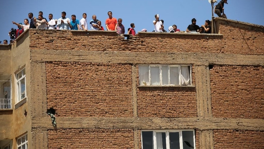 Residents on a nearby rooftop view damage in parts of the historic district of the mainly Kurdish city of Diyarbakir, southeastern Turkey, Sunday, May 22, 2016. Turkish authorities have lifted a long-standing curfew from parts of the historic district famed for its ancient city walls listed as a UNESCO World Heritage site, following its security operations to flush out fighters thought to have links with a Kurdish armed movement. (AP Photo/Mahmut Bozarslan)