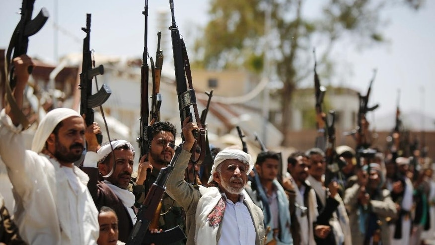 FILE- In this Thursday, May 19, 2016 file photo, Shiite Houthi tribesmen hold their weapons as they chant slogans during a tribal gathering showing support for the Houthi movement, in Sanaa, Yemen. During a Saturday, May 21, 2016 meeting in the Qatari capital, Doha, with U.N. Secretary-General Ban Ki-moon and the emir of Qatar, Yemeni President Abed Rabbo Mansour Hadi agreed to send the government delegation back to the talks, according to a U.N. statement. (AP Photo/Hani Mohammed, File)