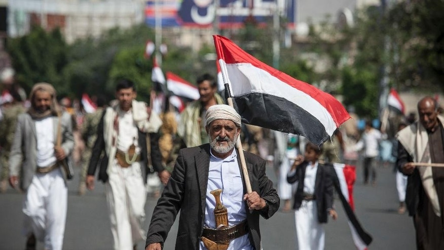 FILE- In this Sunday, May 22, 2016 file photo, a man holds Yemen's flag during a ceremony to commemorate the 26th anniversary of Yemen's reunification, in Sanaa, Yemen. During a Saturday, May 21, 2016 meeting in the Qatari capital, Doha, with U.N. Secretary-General Ban Ki-moon and the emir of Qatar, Yemeni President Abed Rabbo Mansour Hadi agreed to send the government delegation back to the talks, according to a U.N. statement. (AP Photo/Hani Mohammed, File)