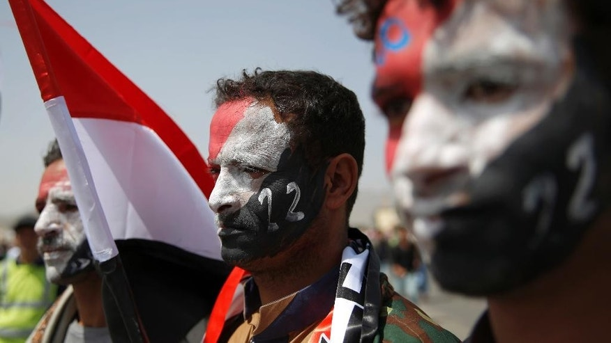 Men with Yemen's flag painted on their faces attend a ceremony to commemorate the 26th anniversary of Yemen's reunification, in Sanaa, Yemen, Sunday, May 22, 2016. South and North Yemen were independent states until unification in 1990. (AP Photo/Hani Mohammed)