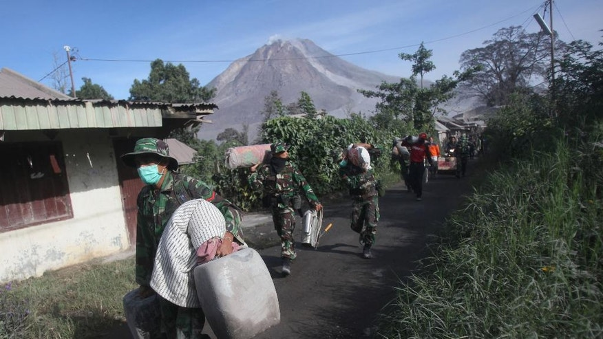 Indonesian soldiers carry people's belongings during an evacuation following the eruption of Mount Sinabung in Gamber village, North Sumatra, Indonesia, Sunday, May 22, 2016. The volcano in western Indonesian unleashed hot clouds of ash on Saturday, killing several villagers, officals said. (AP Photo/Binsar Bakkara)