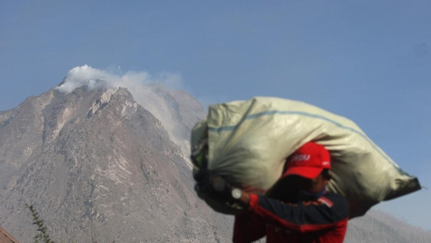 A villager carries his belonging during an evacuation following the eruption of Mount Sinabung in Gamber village, North Sumatra, Indonesia, Sunday, May 22, 2016. The volcano in western Indonesian unleashed hot clouds of ash on Saturday, killing several villagers, oficials said. (AP Photo/Binsar Bakkara)