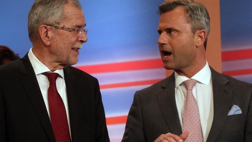 FILE In this April 24, 2016 file picture Alexander Van der Bellen,, left, talks with Norbert Hofer, right, of Austria's Freedom Party, FPOE, during the release of the first results of the first round  of Austria presidential elections in Vienna. Nearly final results for Austria's presidential election Sunday May 22, 2016  showed a right-wing politician neck-to-neck race with a challenger whose views stand in direct opposition to his rival's anti-immigrant and Eurosceptic message. With 97 percent of the vote counted, right-winger Norbert Hofer and Alexander Van der Bellen, a Greens politician running as an independent, each had 50 percent support. (AP Photo/Ronald Zak,File)