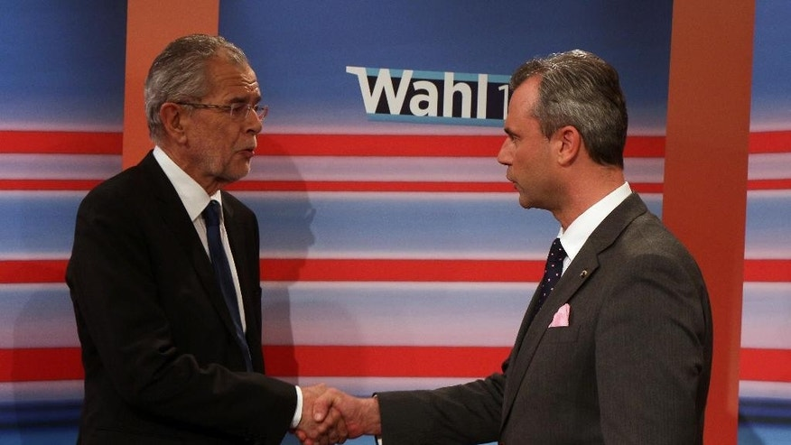 Alexander Van der Bellen candidate of the Austrian Greens, left, shakes hands with Norbert Hofer, candidate for president of Austria's Freedom Party, FPOE, during the release of the election results of the Austria presidential elections in Vienna, Austria, Sunday, May 22, 2016. Nearly final results for Austria's presidential election Sunday showed a right-wing politician neck-to-neck race with a challenger whose views stand in direct opposition to his rival's anti-immigrant and Eurosceptic message. (AP Photo/Ronald Zak)