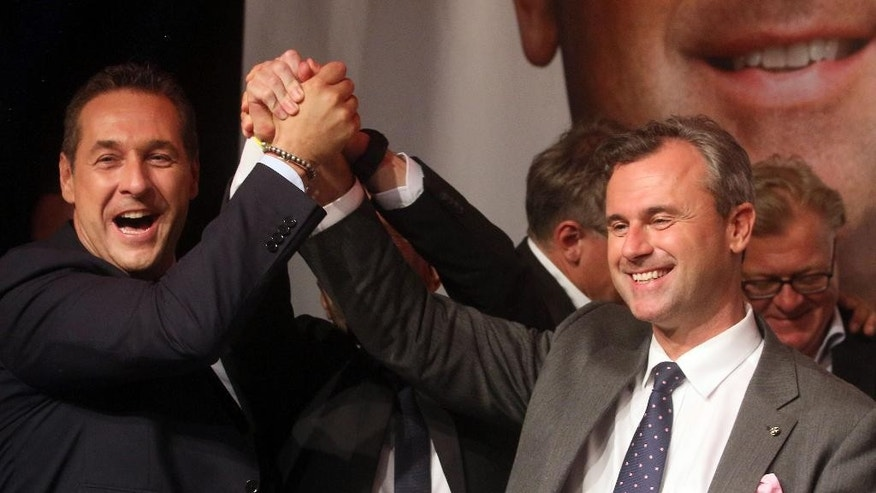 Heinz-Christian Strache, head of Austria's Freedom Party, FPOE, left, congratulates Norbert Hofer, candidate for Austria's Presidency during an after presidential election party in Vienna, Austria, Sunday, May 22, 2016. With all direct ballots counted in today's presidential election, both candidates, right-winger Norbert Hofer and a Greens politician Alexander Van der Bellen, had 50 percent of the vote. Nearly 900,000 absentee ballots are due to be counted tomorrow. (AP Photo/Ronald Zak)