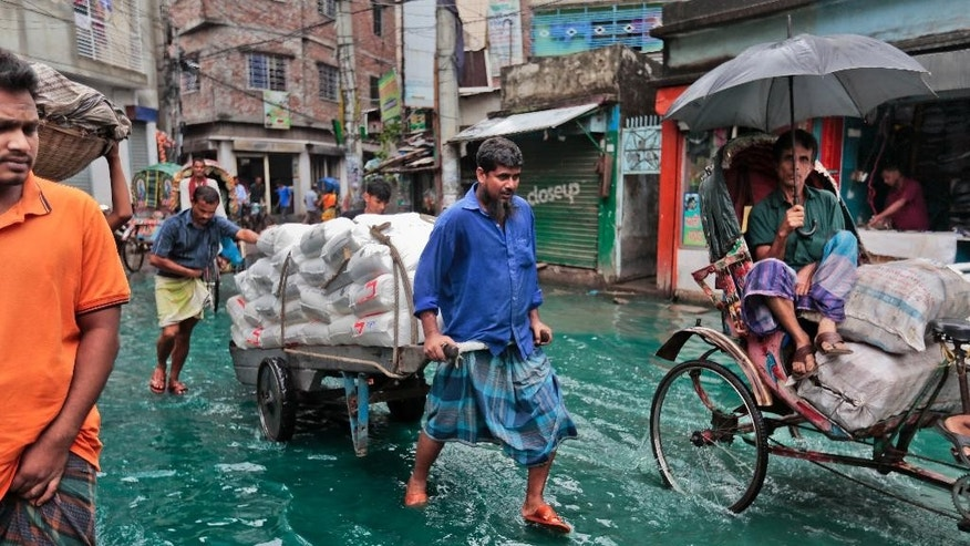Bangladeshi men pull a loaded cart through a waterlogged street after heavy rainfall in Dhaka, Bangladesh, Saturday, May 21, 2016. A cyclone unleashed heavy rain and strong winds on Bangladesh's southern coastal region on Saturday, killing at least 11 people and forcing hundreds of thousands from their homes. Mixing of rain water and toxic waste from industries has turned water into green. (AP Photo/ A.M. Ahad)