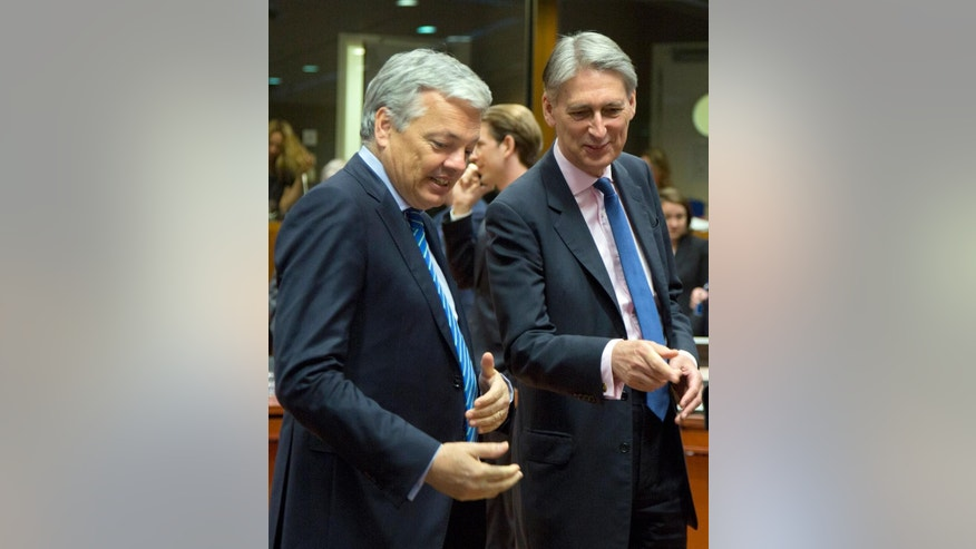 British Foreign Minister Philip Hammond, right, speaks with Belgian Foreign Minister Didier Reynders during a round table meeting of EU foreign ministers at the EU Council building in Brussels on Monday, May 23, 2016. Libya has given the European Union a green light to begin training its coast guard, as increasing numbers of migrants leave the country bound for Italy. (AP Photo/Virginia Mayo)