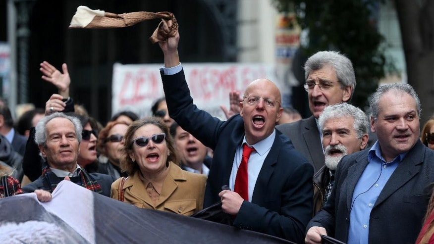 "FILE - In this Thursday, Feb. 4, 2016 file photo, a lawyer waves his tie as others shout shout slogans during a 24-hour nationwide general strike in Athens. Greek lawyers have been on strike for four months against austerity measures that impose heavy taxes on self-employed professionals. Greek lawyers have been on strike for four months against austerity measures that impose heavy taxes on self-employed professionals. Prime minister Alexis Tsipras won a vote in parliament early Monday May 23, 2016, that will heap more taxes on a dwindling number of Greeks able to pay them. Whereas previous protests against austerity cuts drew violent street demonstrations featuring hooded youths throwing firebombs, this time it's suited middle classes professionals revolting in what's been dubbed the ""necktie movement"".  (AP Photo/Petros Giannakouris, File)"