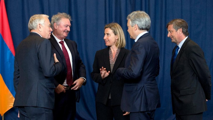 European Union High Representative Federica Mogherini, center, speaks with, from left, French Foreign Minister Jean-Marc Ayrault, Luxembourg's Foreign Minister Jean Asselborn, Belgian Foreign Minister Didier Reynders and Slovenian Foreign Minister Karl Erjavec prior to a group photo of EU foreign ministers at the EU Council building in Brussels on Monday, May 23, 2016. Libya has given the European Union a green light to begin training its coast guard, as increasing numbers of migrants leave the country bound for Italy. (AP Photo/Virginia Mayo)
