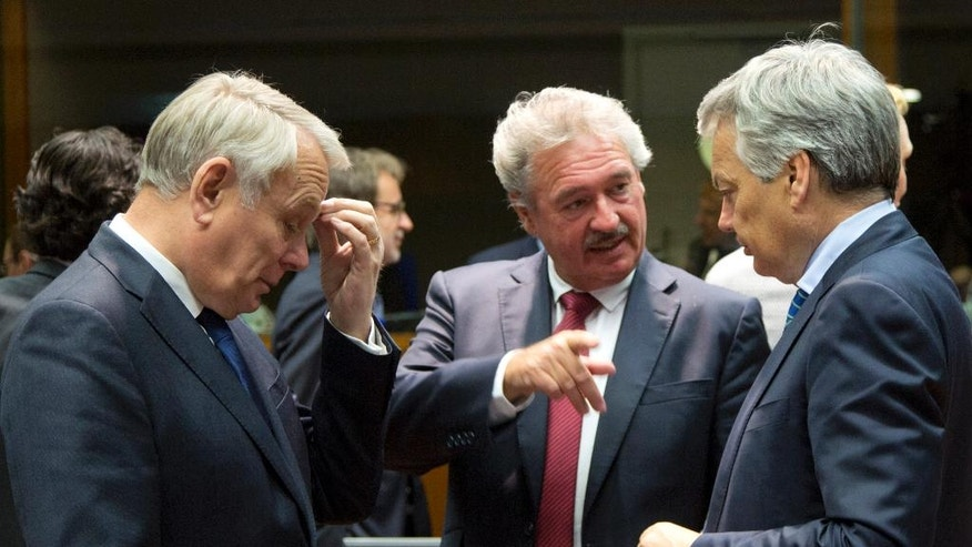 French Foreign Minister Jean-Marc Ayrault, left, speaks with Luxembourg's Foreign Minister Jean Asselborn, center, and Belgian Foreign Minister Didier Reynders during a round table meeting of EU foreign ministers at the EU Council building in Brussels on Monday, May 23, 2016. Libya has given the European Union a green light to begin training its coast guard, as increasing numbers of migrants leave the country bound for Italy. (AP Photo/Virginia Mayo)