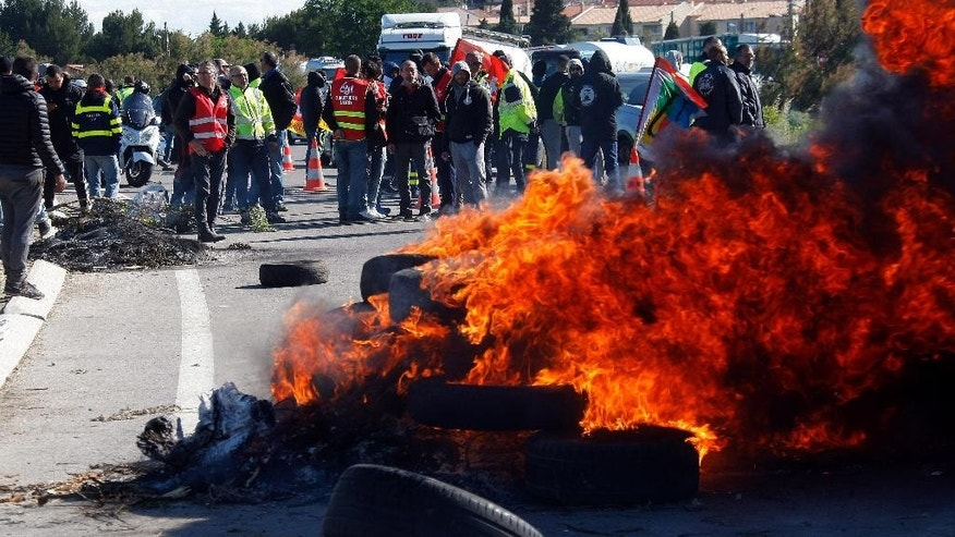 Union members on strike stand near burning barricade preventing the access to a refinery in Fos sur Mer, southern France, Monday, May 23, 2016.  Union-led blockades of French depots and oil refineries have led to fuel shortages and police action. (AP Photo/Claude Paris)