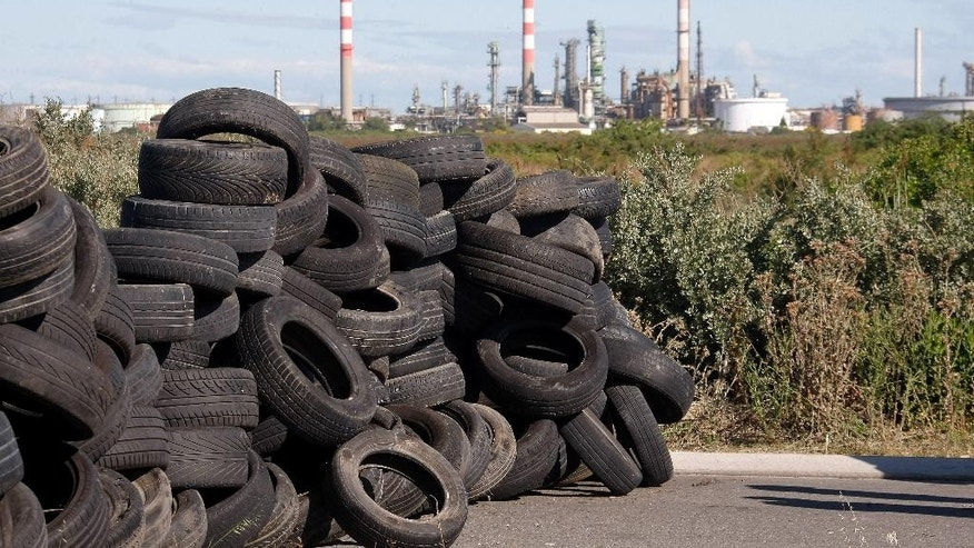 Union members on strike set up a pile of tires to block the entrance of a road leading to a refinery, background, in Fos sur Mer, southern France, Monday, May 23, 2016.  Union-led blockades of French depots and oil refineries have led to fuel shortages and police action. (AP Photo/Claude Paris)