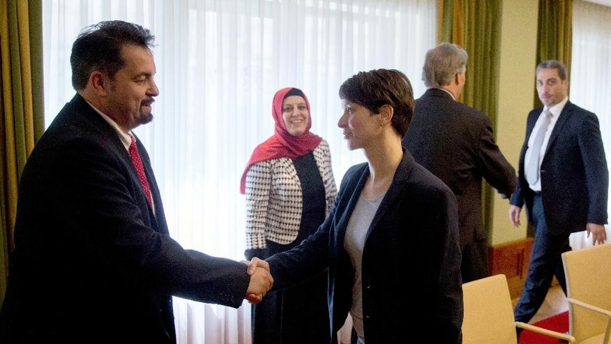 Chairwoman of the right-wing populist party Alternative for Germany , AfD,  Frauke Petry, right, and the chairman of the Central Council of Muslims in Germany  Aiman Mazyek , left, shake hands at the start of the meeting in Berlin, Germany, Monday May 23,  2016.   (Kay Nietfeld/dpa via AP)