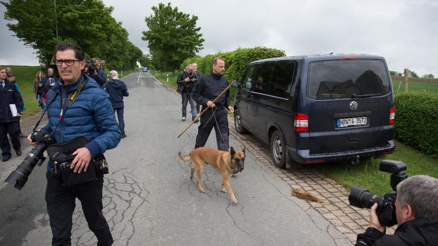 Sniffer dog Sunny and dog handler Ulrich Hitzemann look for traces  on a street in Hoexter  Germany, Monday,  May 23, 2016. Police with sniffer dogs are  searching a road in western Germany for traces of the remains of a woman  believed to have been killed and dismembered two years ago by a couple also  suspected in another death. Officers on Monday searched a 2-kilometer (1 1/4-mile) stretch of road near the home of  the suspects outside the town of Hoexter. They're looking for tooth or bone fragments from the victim. (Friso Gentsch/dpa via AP)