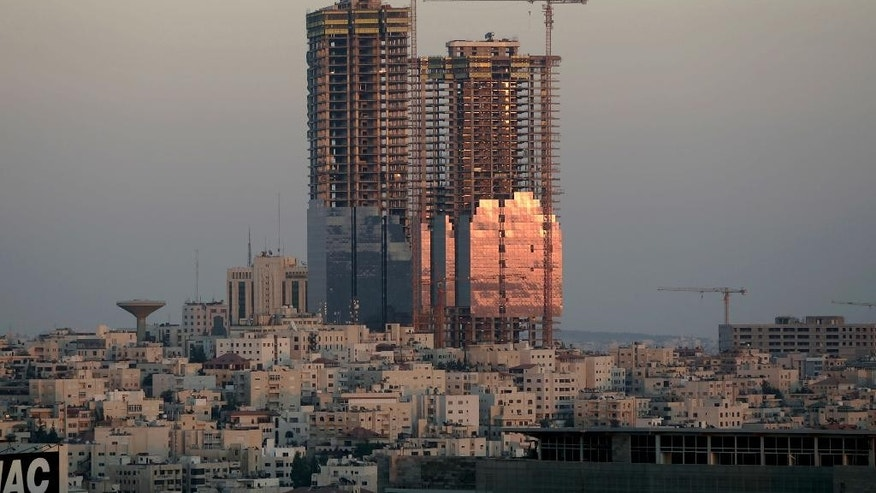 FILE -- In this Sunday, July 6. 2008 file photo, the sunset reflects on the Jordan Gate Towers under construction in Amman, Jordan. Murad Awamleh, a senior official in the Amman municipality, said Monday, May 23, 2016 that work will resume on the half-built twin towers that have blighted the skyline of the Jordanian capital for years, a symbol of mega construction schemes gone awry. The official said the Gulf-based Al Bayan Holding Company, and a Jordanian firm, Al Hamad Contracting, reached a deal to complete the Jordan Gate Towers within two years for $120 million. (AP Photo/Nader Daoud, File)