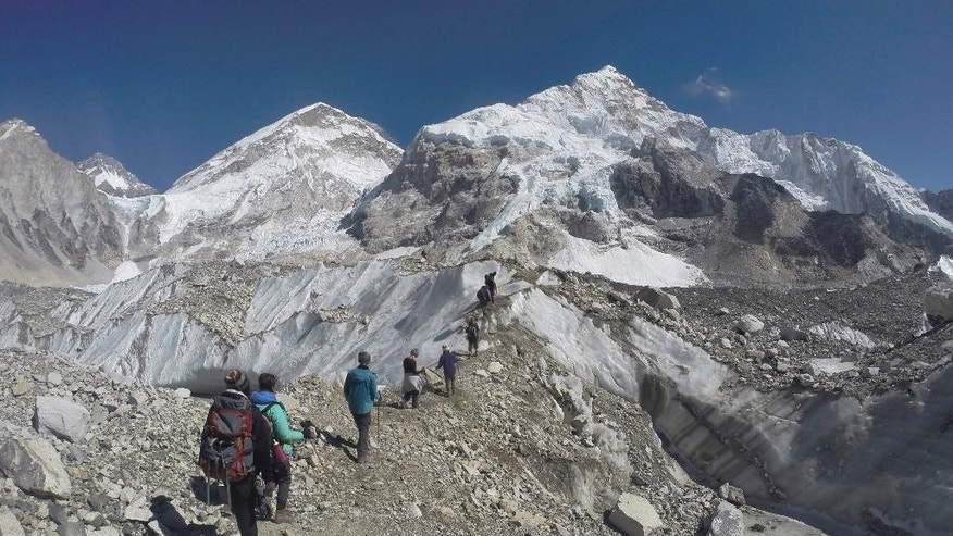 FILE - In this Monday, Feb. 22, 2016 file photo, international trekkers pass through a glacier at the Mount Everest base camp, Nepal. An Indian climber has died while being helped down Mount Everest, just hours after a Dutch and an Australian climber died near the peak. Poor planning and overcrowding on the world's tallest peak may have led to bottlenecks that kept people delayed at the highest reaches while waiting for the path to clear lower down, Ang Tshering of the Nepal Mountaineering Association said Monday, May 23. (AP Photo/Tashi Sherpa, File)