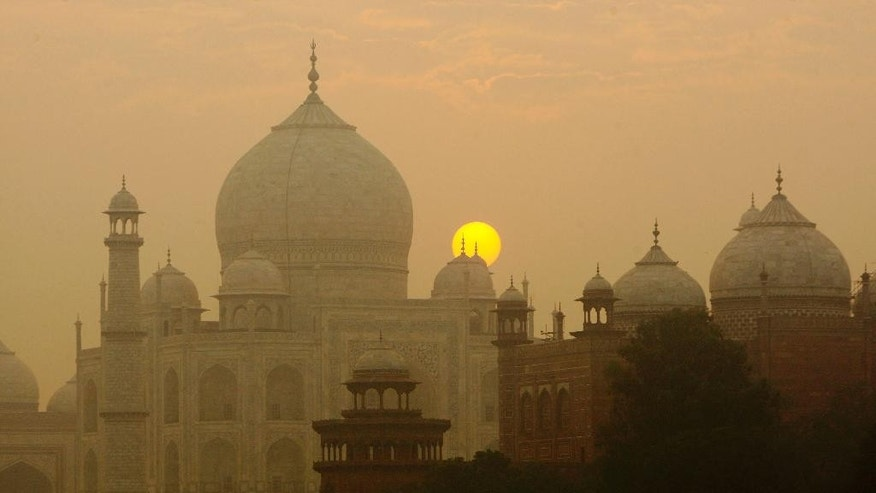 FILE - In this Nov. 18, 2009, file photo, the sun rises over the Taj Mahal in Agra, India. Archaeological experts say insects proliferating from a polluted river near the Taj Mahal are marring the intricate marble inlay work by leaving greenish black patches of waste on the walls of the 17th century monument of love. (AP Photo/Gurinder Osan, File)