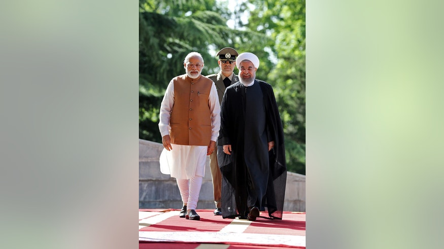 Indian Prime Minister Narendra Modi, left, walks with Iranian President Hassan Rouhani during an official welcoming ceremony at the Saadabad Palace in Tehran, Iran, Monday, May 23, 2016. (Iranian Presidency Office via AP)