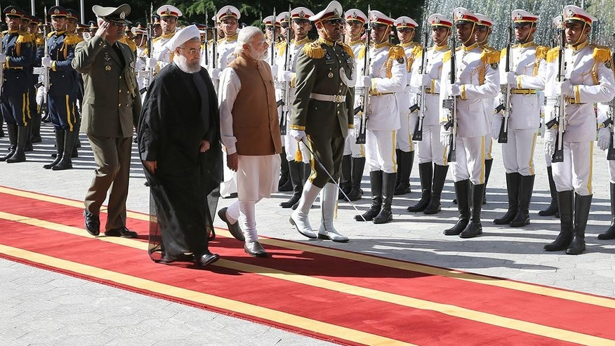 Indian Prime Minister Narendra Modi, third left, reviews an honor guard as he is welcomed by Iranian President Hassan Rouhani, second left, during an official welcoming ceremony at the Saadabad Palace in Tehran, Iran, Monday, May 23, 2016. (Iranian Presidency Office via AP)