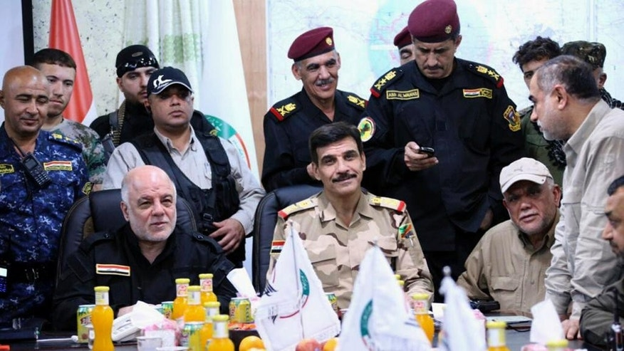 This picture provided by the office of Iraq's Prime Minister, shows Iraqi Prime Minister Haider al-Abadi, seated left, wearing a black uniform and flanked by senior military commanders during a meeting at the Fallujah Operation Command center outside Fallujah, Iraq, Monday, May 23, 2016. Iraqi government forces on Monday pushed Islamic State militants out of some agricultural areas outside Fallujah as they launched a military offensive to recapture the city from the extremists, officials said. (Iraqi Prime Minister's Office via AP)