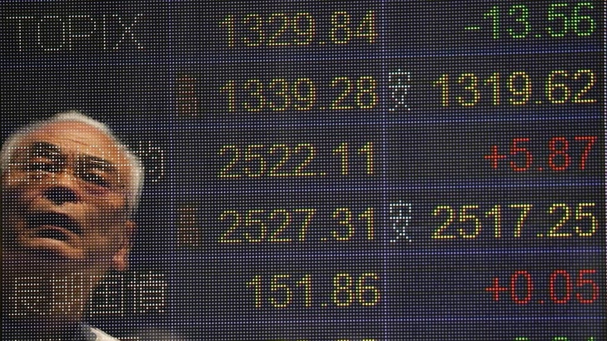 A man is reflected on the electronic board of a securities firm in Tokyo, Monday, May 23. 2016. Japanese stocks fell and other Asian markets were higher Monday after a global finance meeting failed to produce an economic growth plan and Tokyo reported weaker exports. (AP Photo/Koji Sasahara)