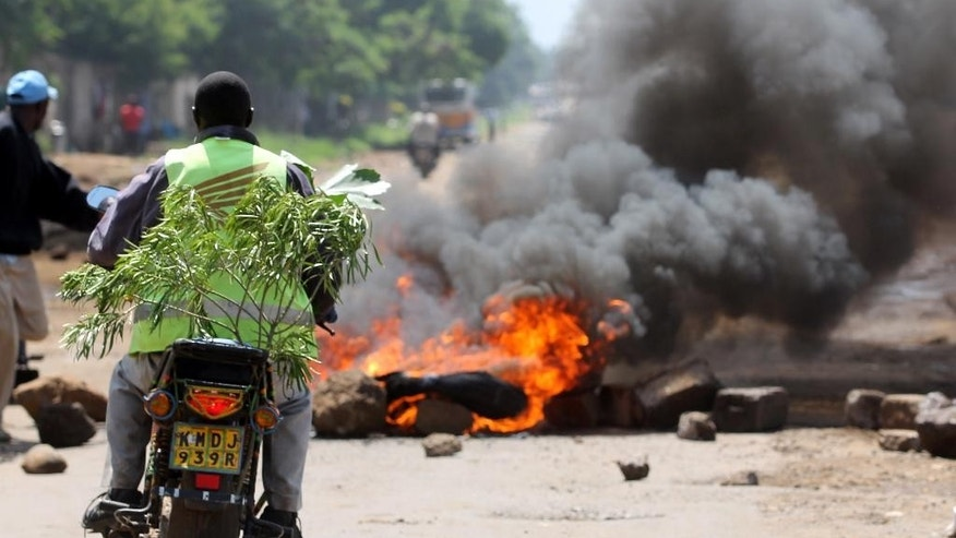 A Kisumu resident stops on his bike to look at burning tyres in the street following protests in Kisumu, Kenya, Monday May 23, 2016. The protests, held for the past four weeks, come before elections next year and are organized by Kenya's main opposition group the Coalitions for Reforms and Democracy. (AP Photo/James Kayee)