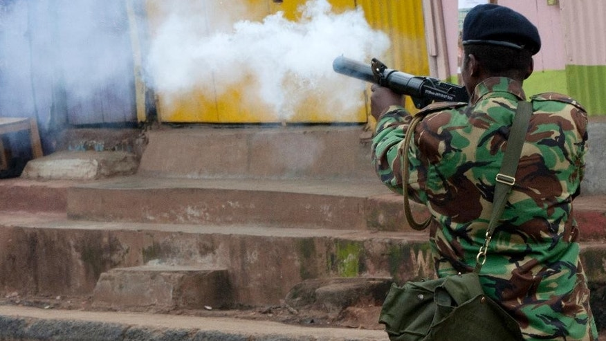 A riot police officer fires a teargas canister during a protest in Kibera Slums, Nairobi, Kenya Monday, May 23, 2016. The protests, held every Monday for the past four weeks, come before elections next year and are organized by Kenya's main opposition group the Coalitions for Reforms and Democracy. (AP Photo/Sayyid Azim)