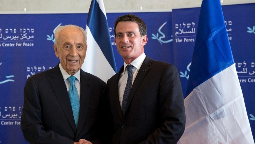 Former Israeli President Shimon Peres, left, and French Prime Minister Manuel Valls shake hands ahead of their meeting at the Peres Center for Peace in Tel Aviv, Israel, Sunday, May 22, 2016. (AP Photo/Ariel Schalit)