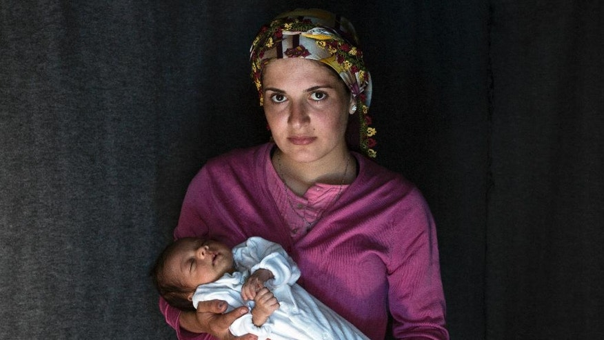 In this photo taken on Friday, May 13, 2016, 23-year-old Rojin, a Kurdish-Syrian mother from the city of Qamishli, Syria, poses with her baby girl Beritan in a tent made of blankets given by the UNCHR at the refugee camp of the northern Greek border point of Idomeni. Rojin is one of the dozens of refugee women that gave birth while stranded in Idomeni after the Greek- Macedonian border was closed in early March 2016. Berating, the family's first child, was born on Sunday, April 10, 2016 in the hospital of the nearby town of Kilkis. The three member family wants to go to Switzerland. (AP Photo/Petros Giannakouris)