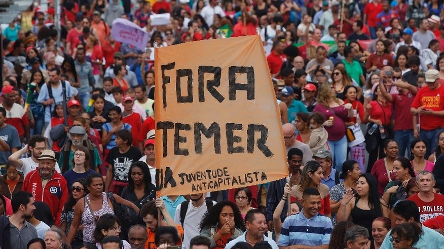 "With a sign that reads in Portuguese ""Temer out,"" demonstrators march against Brazil's acting President Michel Temer and in support of Brazil's suspended President Dilma Rousseff, in Sao Paulo, Brazil, Sunday, May 22, 2016. Temer took office after Rousseff was suspended for up to 180 days while the Senate holds an impeachment trial. (AP Photo/Andre Penner)"