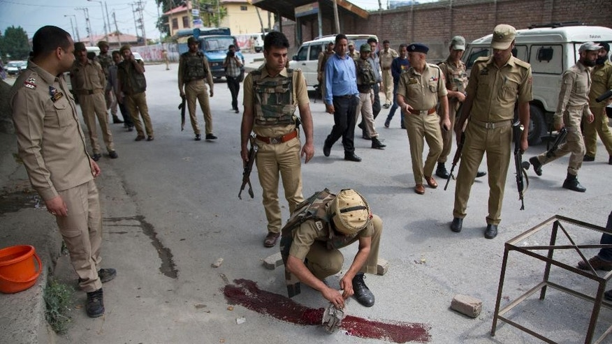 An Indian policeman cleans the ground where police officers were killed when suspected rebels fired at a group of police in Srinagar, Indian controlled Kashmir, Monday, May 23, 2016. Indian security forces are searching the area for the assailants who fled after the attack. (AP Photo/Dar Yasin)