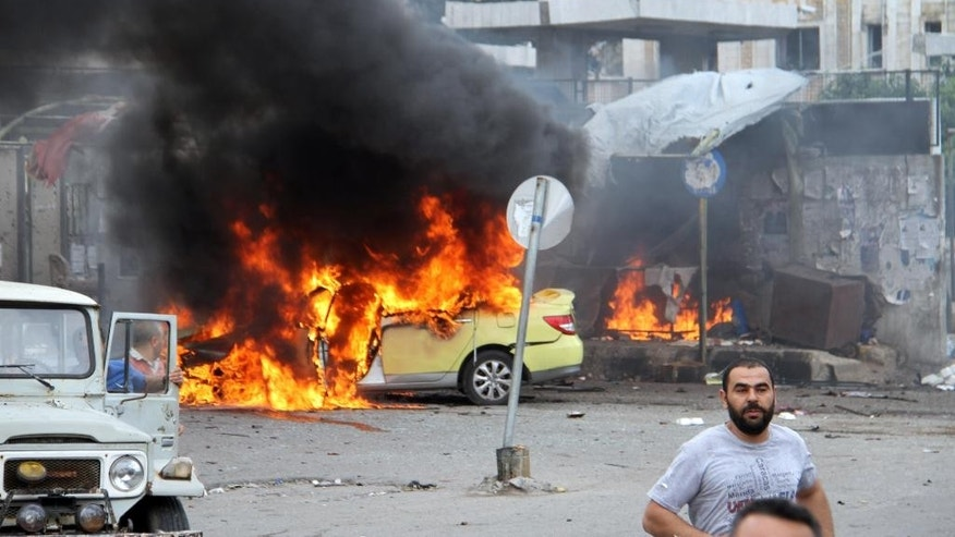 In this photo released by the Syrian official news agency SANA, Syrians gather in front of a burning car at the scene where suicide bombers blew themselves up, in the coastal town of Tartus, Syria, Monday, May 23, 2016. Syrian TV said suicide bombers blew themselves followed by a car bomb in a parking lot packed during morning rush hour. (SANA via AP)