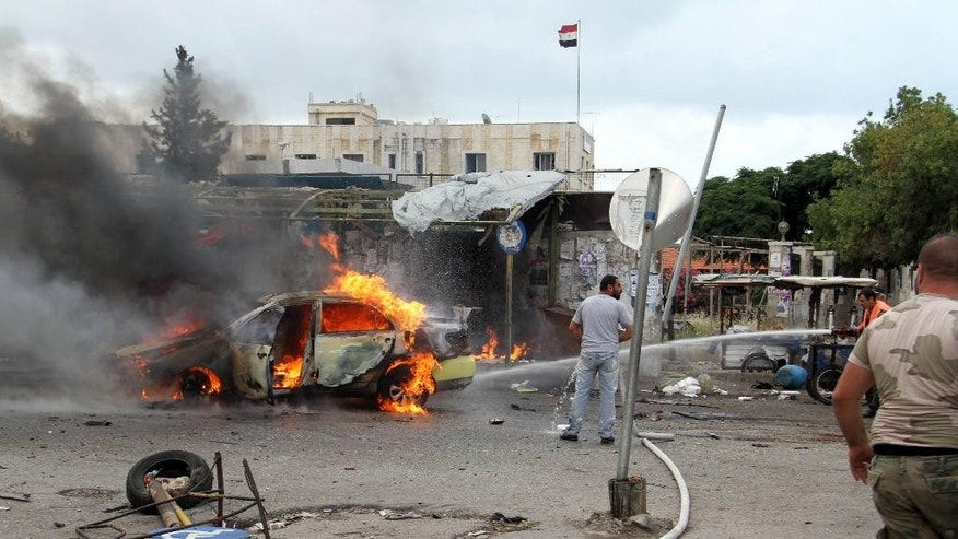 In this photo released by the Syrian official news agency SANA, a firefighter, right, extinguishes a burning car at the scene where suicide bombers blew themselves up, in the coastal towns of Tartus, Syria, Monday, May 23, 2016.  Syrian TV said suicide bombers blew themselves followed by a car bomb in a parking lot packed during morning rush hour. (SANA via AP)
