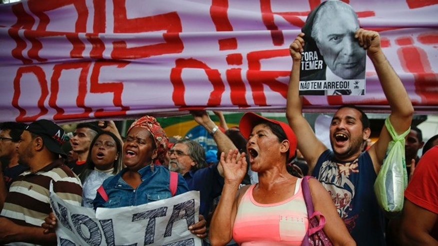 "With signs that read in Portuguese ""Dilma come back"" and ""Temer Out,"" demonstrators shout slogans during a protest against Brazil's acting President Michel Temer and in support of Brazil's suspended President Dilma Rousseff, close to Temer's residence in São Paulo, Brazil, Sunday, May 22, 2016. Temer took office after Rousseff was suspended for up to 180 days while the Senate holds an impeachment trial. (AP Photo/Andre Penner)"