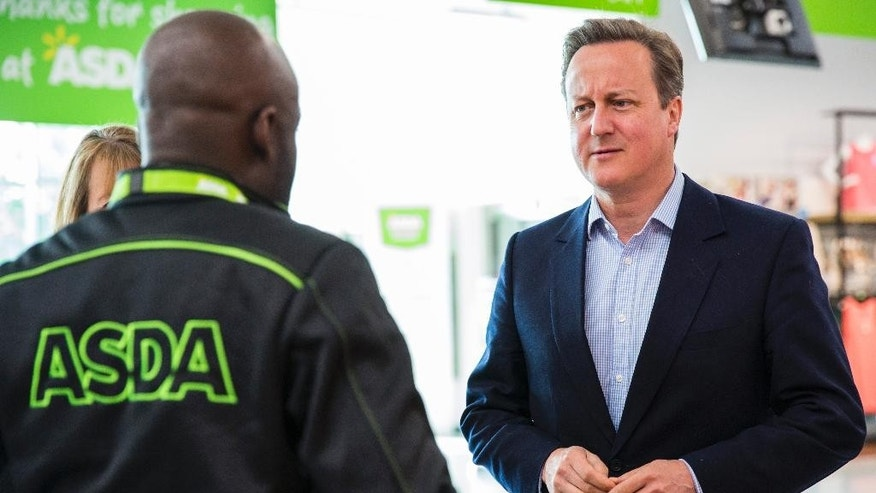 Britain's Prime Minister, David Cameron, right, speaks to a supermarket employee during a visit to a store in the suburb of Hayes, London, Sunday, May 22, 2016. Conservative Cameron and politicians from other political parties are campaigning to remain in the European Union ahead of the EU referendum on June 23. (Jack Taylor/Pool Photo via AP)
