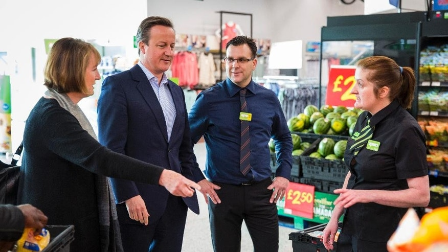 Britain's Prime Minister, David Cameron, 2nd left, speaks to supermarket employees during a visit with former Deputy Labour Party leader, Harriet Harman, left, to a store in the suburb of Hayes, London, Sunday, May 22, 2016. Conservative Cameron and politicians from other political parties are campaigning to remain in the European Union ahead of the EU referendum on June 23. (Jack Taylor/Pool Photo via AP)