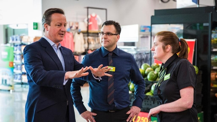 Britain's Prime Minister, David Cameron, left, speaks to supermarket employees during a visit to a store in the suburb of Hayes, London, Sunday, May 22, 2016. Conservative Cameron and politicians from other political parties are campaigning to remain in the European Union ahead of the EU referendum on June 23. (Jack Taylor/Pool Photo via AP)