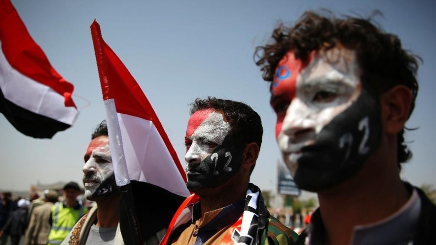 Men with Yemen's flag painted on their faces, attend a ceremony to commemorate the 26th anniversary of Yemen's reunification, in Sanaa, Yemen, Sunday, May 22, 2016. South and North Yemen were independent states until unification in 1990. (AP Photo/Hani Mohammed)