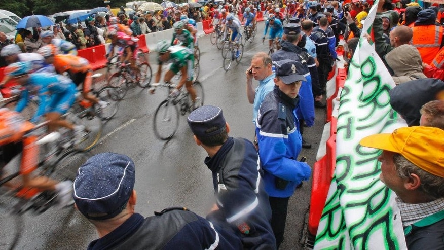 FILE - This Monday July 7, 2008 file photo shows French police holding back demonstrating harbor workers during the third stage of the Tour de France cycling race between Saint-Malo and Nantes, western France. Cyclists at this year's Tour de France will be under the watch of 23,000 police, including SWAT-like intervention squads, as the government tries to ensure security amid extremist threats. (AP Photo/Christophe Ena, File)