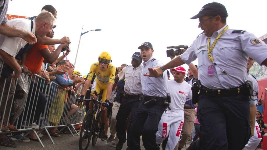 FILE - This Saturday July 21, 2012file photo shows Bradley Wiggins of Britain, wearing the overall leader's yellow jersey, escorted by French police after crossing the finish line of the 19th stage of the the Tour de France cycling race, an individual time trial over 53.5 kilometers (33.2 miles) with start in Bonneval and finish in Chartres, France. Cyclists at this year's Tour de France will be under the watch of 23,000 police, including SWAT-like intervention squads, as the government tries to ensure security amid extremist threats. (AP Photo/Peter Dejong, File)