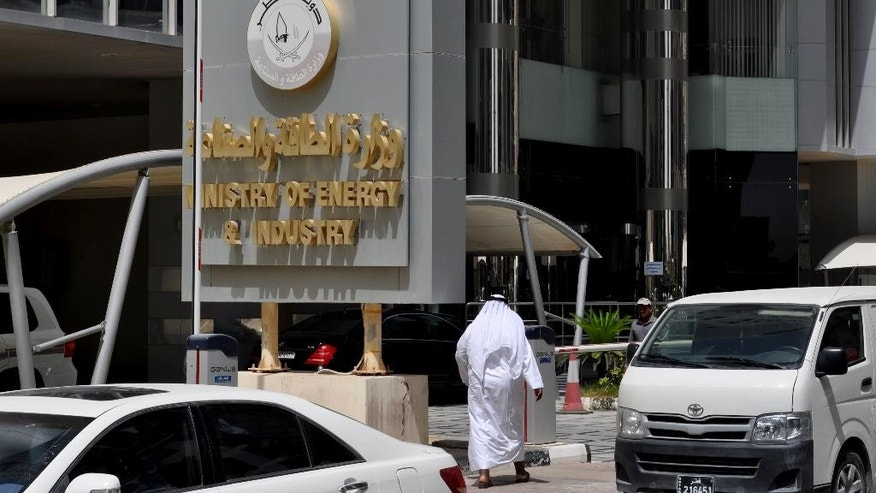 """A Qatari man walks past the country's Ministry of Energy and Industry in Doha, Qatar, Tuesday, May 24, 2016. Mohammed bin Saleh al-Sada, Qatar's minister of energy and industry, says the oil market is recovering slowly from its steep drop over the past two years but crude is still not trading at a """"fair price"""" to encourage necessary investment. (AP Photo/Adam Schreck)"""