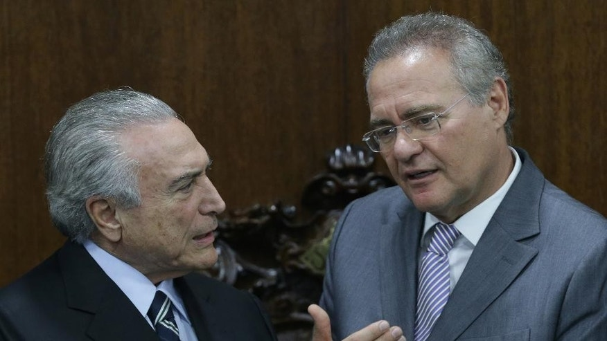 Brazil's acting President Michel Temer, left, talks with President of the National Congress Sen. Renan Calheiros, during meeting to deliver to Congress the revision project of the government's fiscal target, in Brasilia, Brazil, Monday, May 23, 2016. Brazil's interim government is under fire after a recording emerged of the planning minister discussing a purported pact to push for President Dilma Rousseff's impeachment to stall a massive corruption probe. (AP Photo/Eraldo Peres)