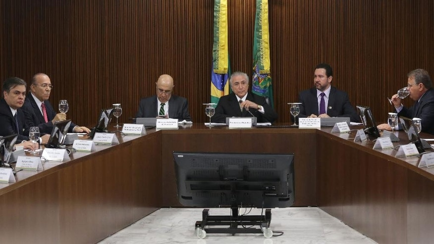 Brazil's acting President Michel Temer, center, holds a meeting on economic measures with party leaders from the Lower House and Senate at Planalto presidential palace in Brasilia, Tuesday, May 24, 2016. Temer announced belt-tightening measures aimed at pulling Latin America's largest economy from its worst crisis in decades, including taking back billions it loaned Brazil's state-run investment bank, abolishing a fund created to channel oil revenues into education, sharply cutting public spending and negotiating reforms to the country's pension system. Temer took over after President Dilma Rousseff was impeached earlier this month for allegedly using accounting tricks in managing the federal budget. (AP Photo/Eraldo Peres)