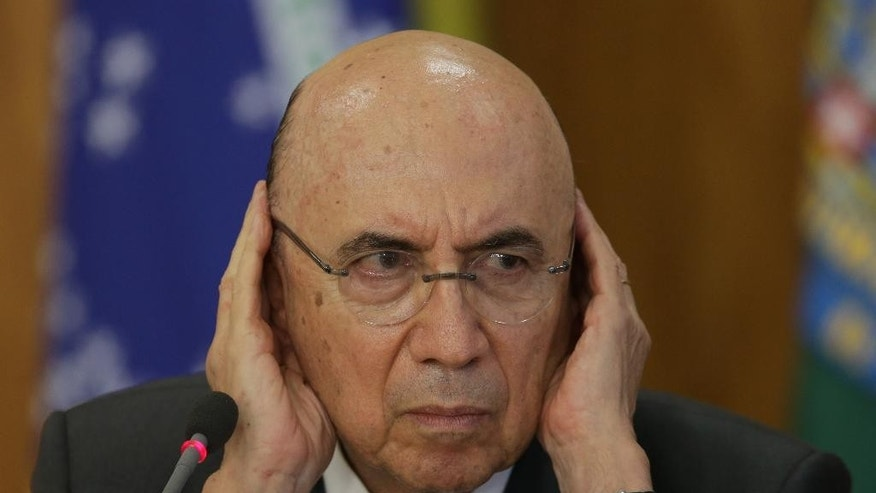 Brazil's Finance Minister Henrique Meirelles cups his ears to hear a journalist's question better during a news conference following a meeting on economic measures with Congressional party leaders at Planalto presidential palace in Brasilia, Tuesday, May 24, 2016. Meirelles and acting President Michel Temer announced belt-tightening measures aimed at pulling Latin America's largest economy from its worst crisis in decades, including taking back billions it loaned Brazil's state-run investment bank, abolishing a fund created to channel oil revenues into education, sharply cutting public spending and negotiating reforms to the country's pension system. President Dilma Rousseff was impeached earlier this month for allegedly using accounting tricks in managing the federal budget. (AP Photo/Eraldo Peres)