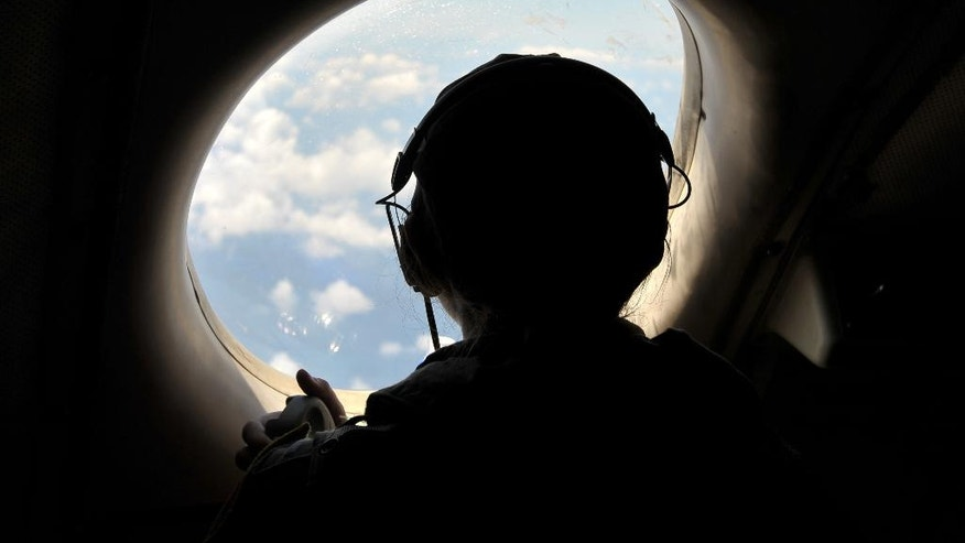U.S. Navy LT JG Katia Medford-Davis looks from a window of a U.S. Navy Lockheed P-3C Orion patrol aircraft from Sigonella, Sicily, Sunday, May 22, 2016, searching the area in the Mediterranean Sea where the Egyptair flight 804 en route from Paris to Cairo went missing on May 19. Search crews found floating human remains, luggage and seats from the doomed EgyptAir jetliner Friday but face a potentially more complex task in locating bigger pieces of wreckage and the black boxes vital to determining why the plane plunged into the Mediterranean. (AP Photo/Salvatore Cavalli)