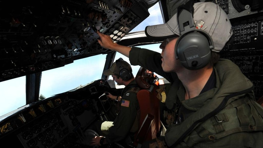 U.S. Navy AWF3 Kevin Cruz, right, touches a control panel of a U.S. Navy Lockheed P-3C Orion patrol aircraft from Sigonella, Sicily, Sunday, May 22, 2016, searching the area in the Mediterranean Sea where the Egyptair flight 804 en route from Paris to Cairo went missing on May 19. Search crews found floating human remains, luggage and seats from the doomed EgyptAir jetliner Friday but face a potentially more complex task in locating bigger pieces of wreckage and the black boxes vital to determining why the plane plunged into the Mediterranean. (AP Photo/Salvatore Cavalli)
