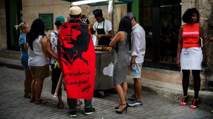 "The Mexican tourist Carlos Lome Morales wears a Che Guevara flag over his shoulders, as he lines up at a street stall to buy churros, in Havana, Cuba,Monday, May 23, 2016. The flag has a quote by Guevara that reads in Spanish ""To victory always."" (AP Photo/Ramon Espinosa)"