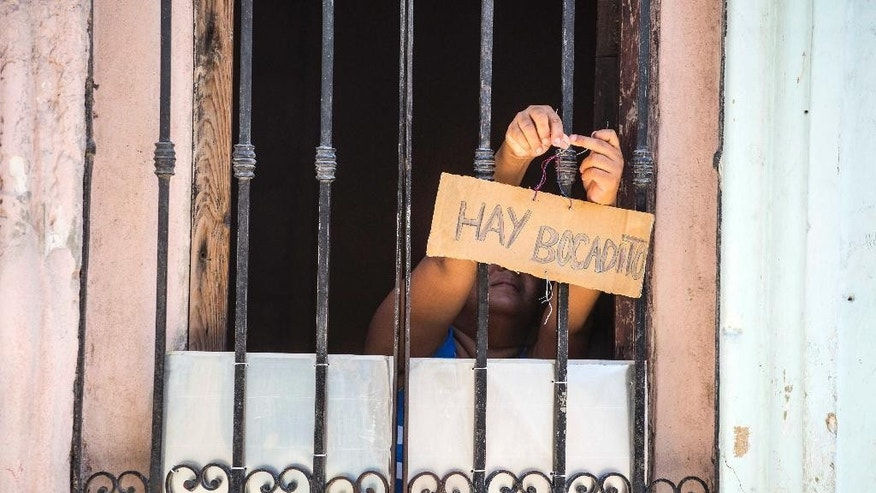 "A woman hangs a sign on her front door that reads in Spanish ""There's sandwiches"" in Havana, Cuba, Tuesday, May 24, 2016. Cuba says it will legalize small and medium-sized private businesses, a move that could significantly expand the space allowed for private enterprise in one of the world's last communist countries. ""This is a tremendously important step,"" said Alfonso Valentin Larrea Barroso, director-general of Scenius, a cooperatively run economic consulting firm in Havana. ""They're creating, legally speaking, the non-state sector of the economy. They're making that sector official."" (AP Photo/Desmond Boylan)"